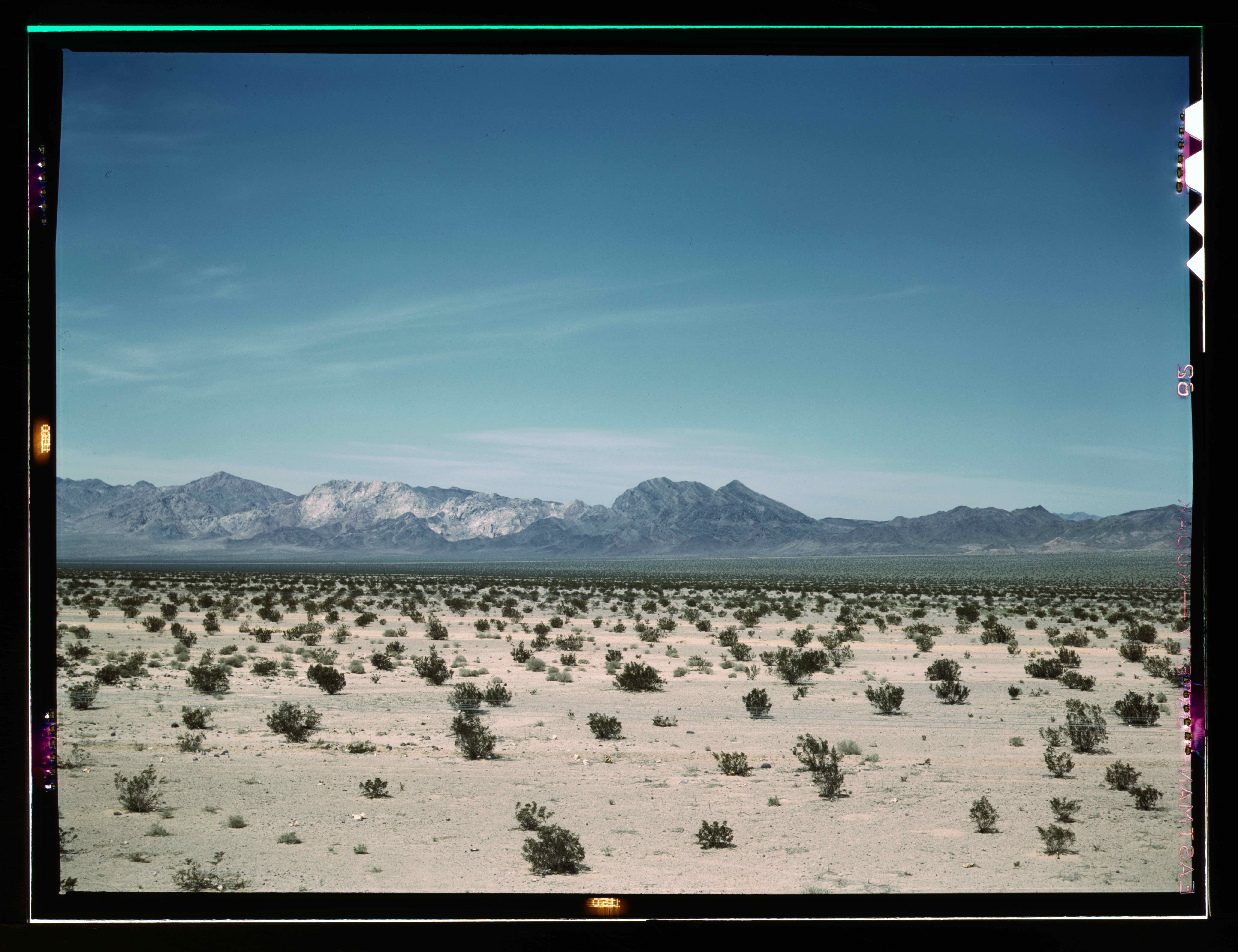 a desert with a mountain range in the distance
